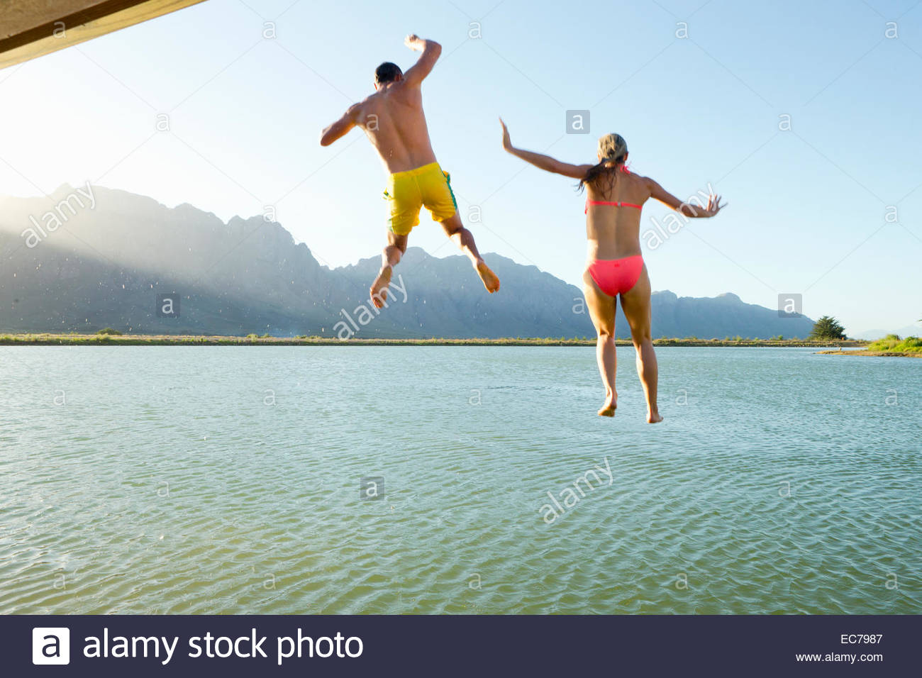 Couple in swimwear, jumping into a lake from a jetty - Stock Image
