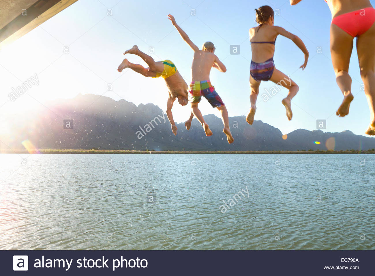 Family, in swimwear, jumping into a lake from a jetty - Stock Image