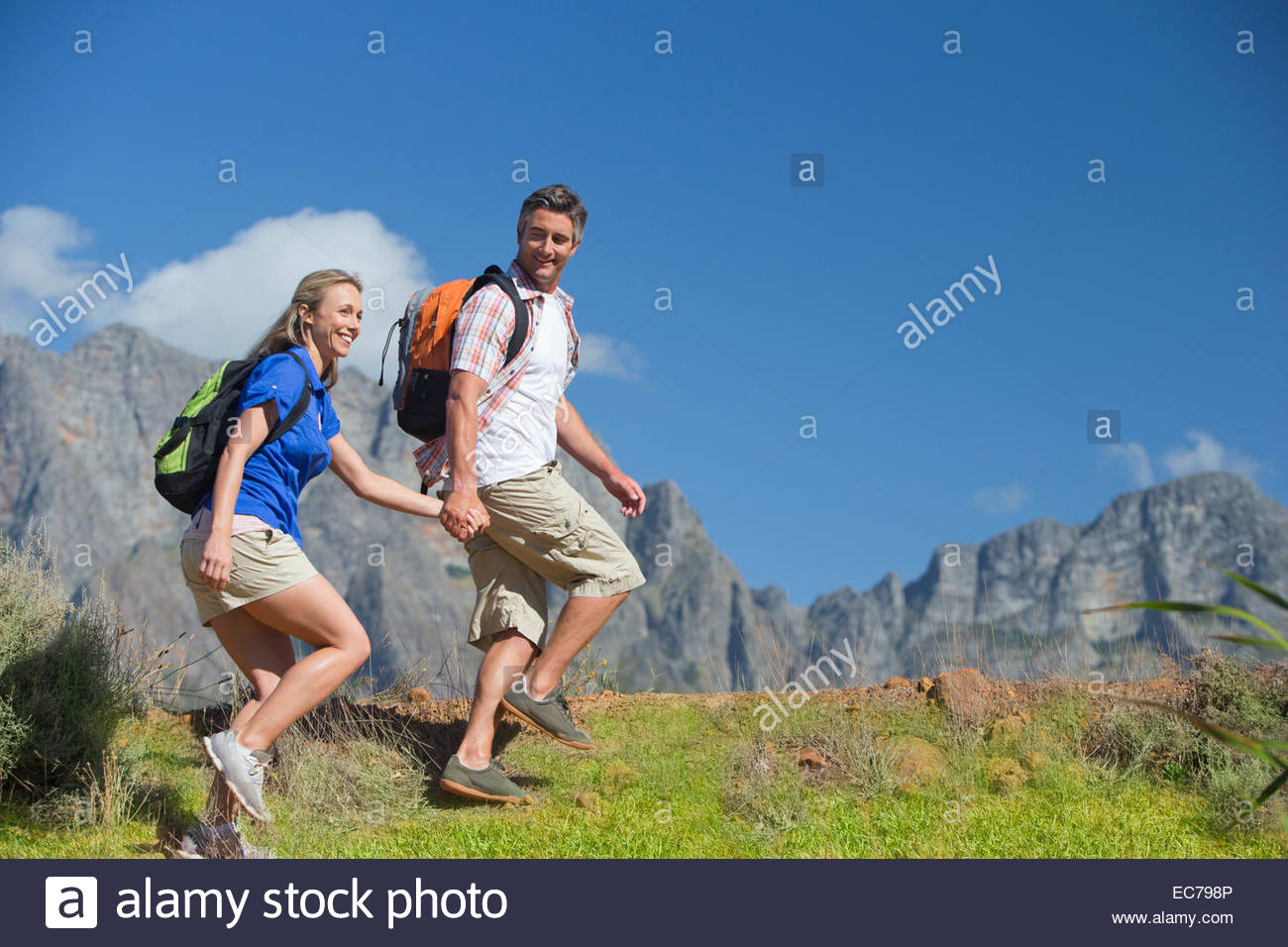 Couple hiking on a mountain path - Stock Image