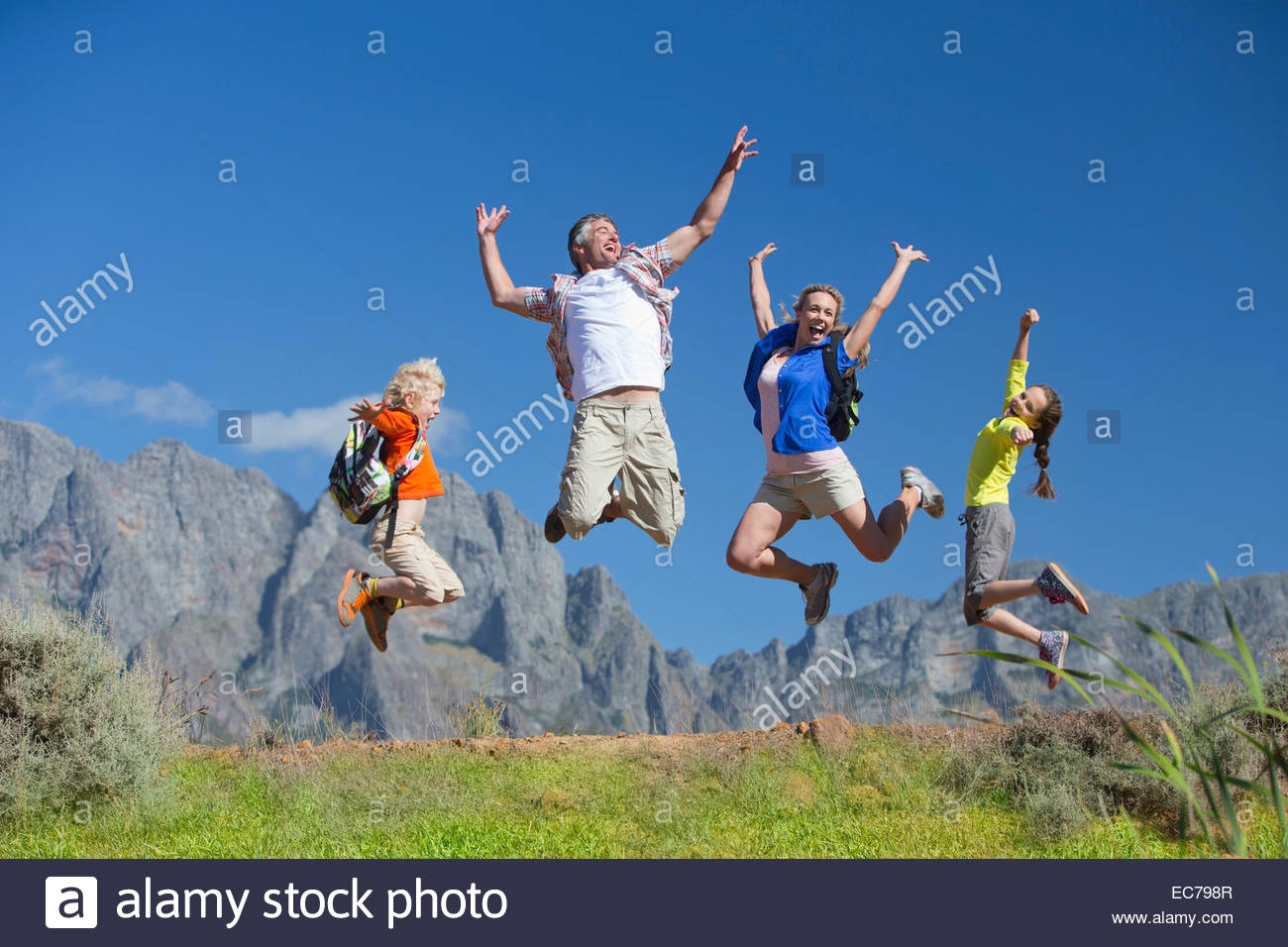 Family jumping in the air on a mountain hiking trail - Stock Image
