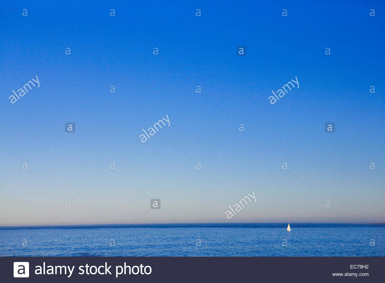 Sail boat in the distance at sea - Stock Image
