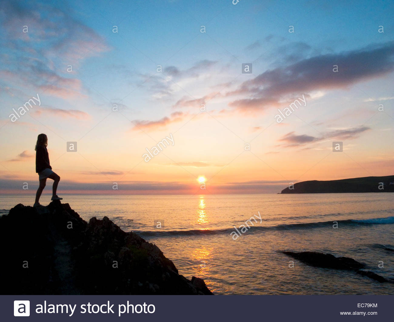 Silhouette of woman looking out to sea at sunset - Stock Image