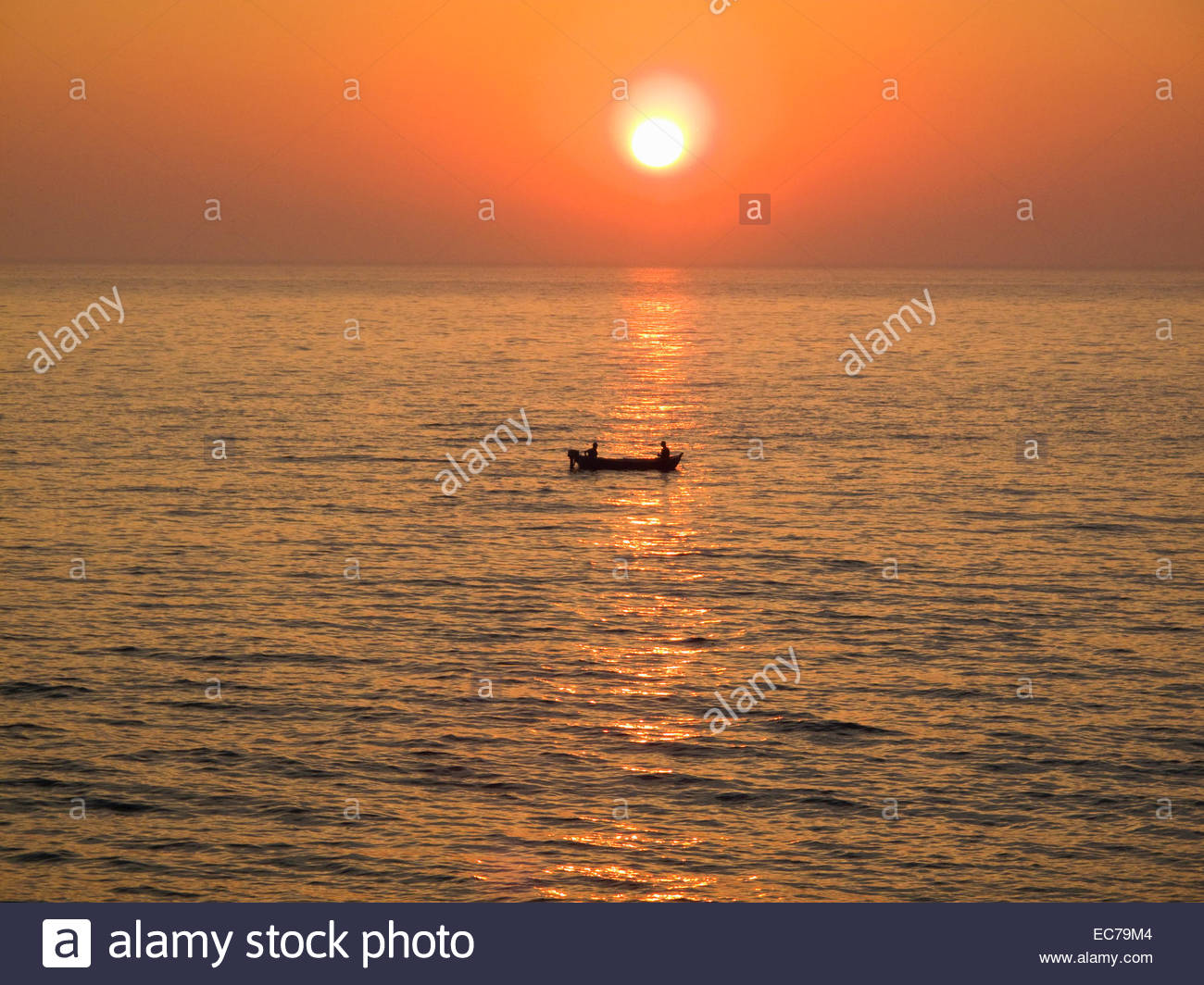 Fishermen in boat at sea with sunset backdrop - Stock Image