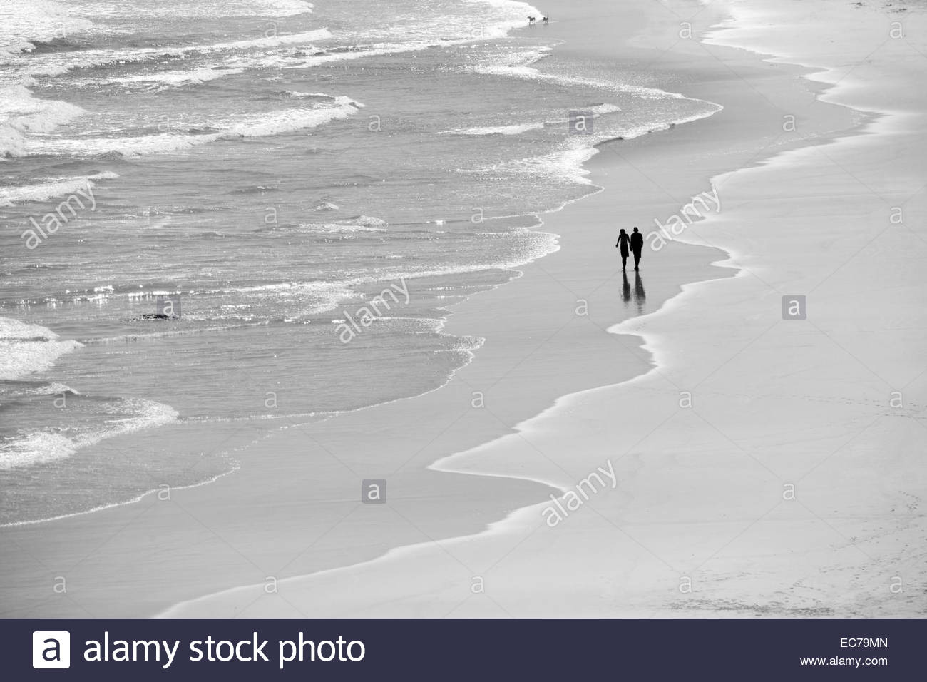 Couple walking along picturesque beach with waves - Stock Image