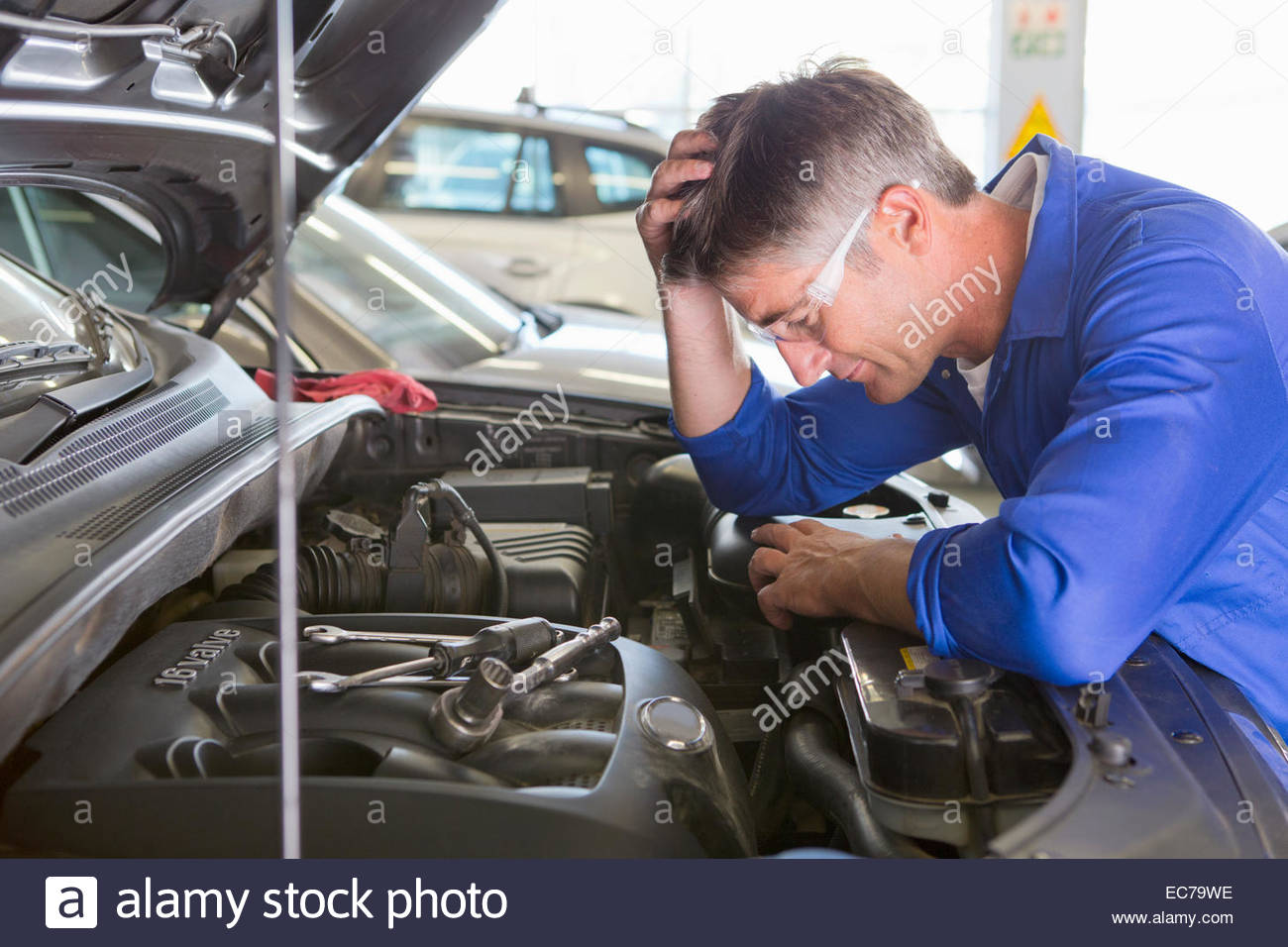 Mechanic baffled by problem with car - Stock Image