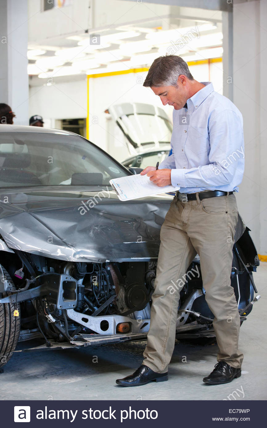 Insurance assessor inspecting damaged vehicle - Stock Image