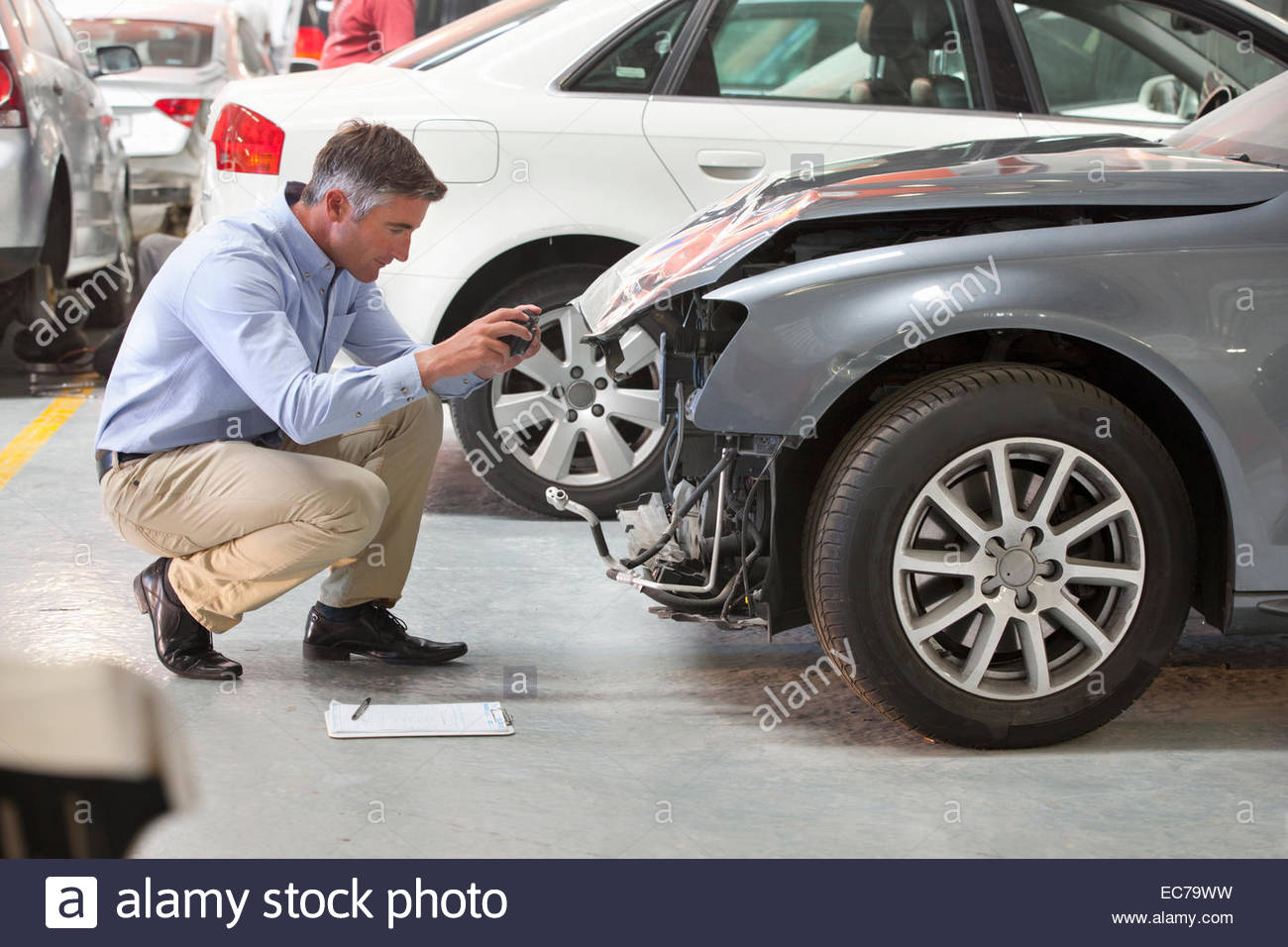 Insurance assessor inspecting damaged vehicle and taking photograph - Stock Image