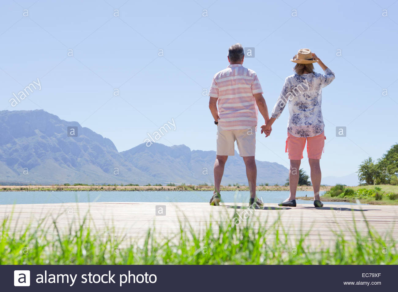 Senior couple standing hand-in-hand on jetty looking at lake - Stock Image