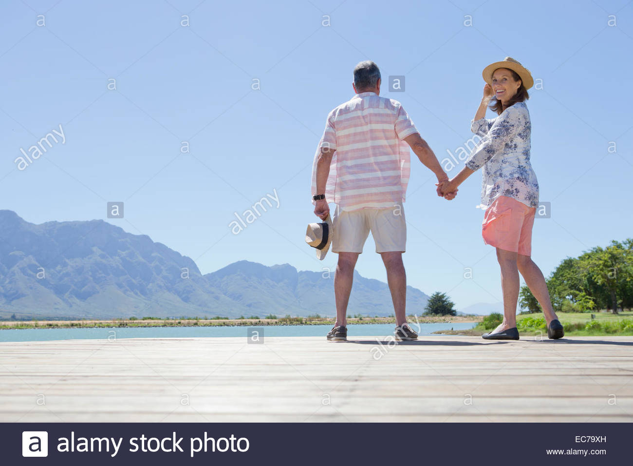 Senior couple standing hand in hand on wooden jetty - Stock Image