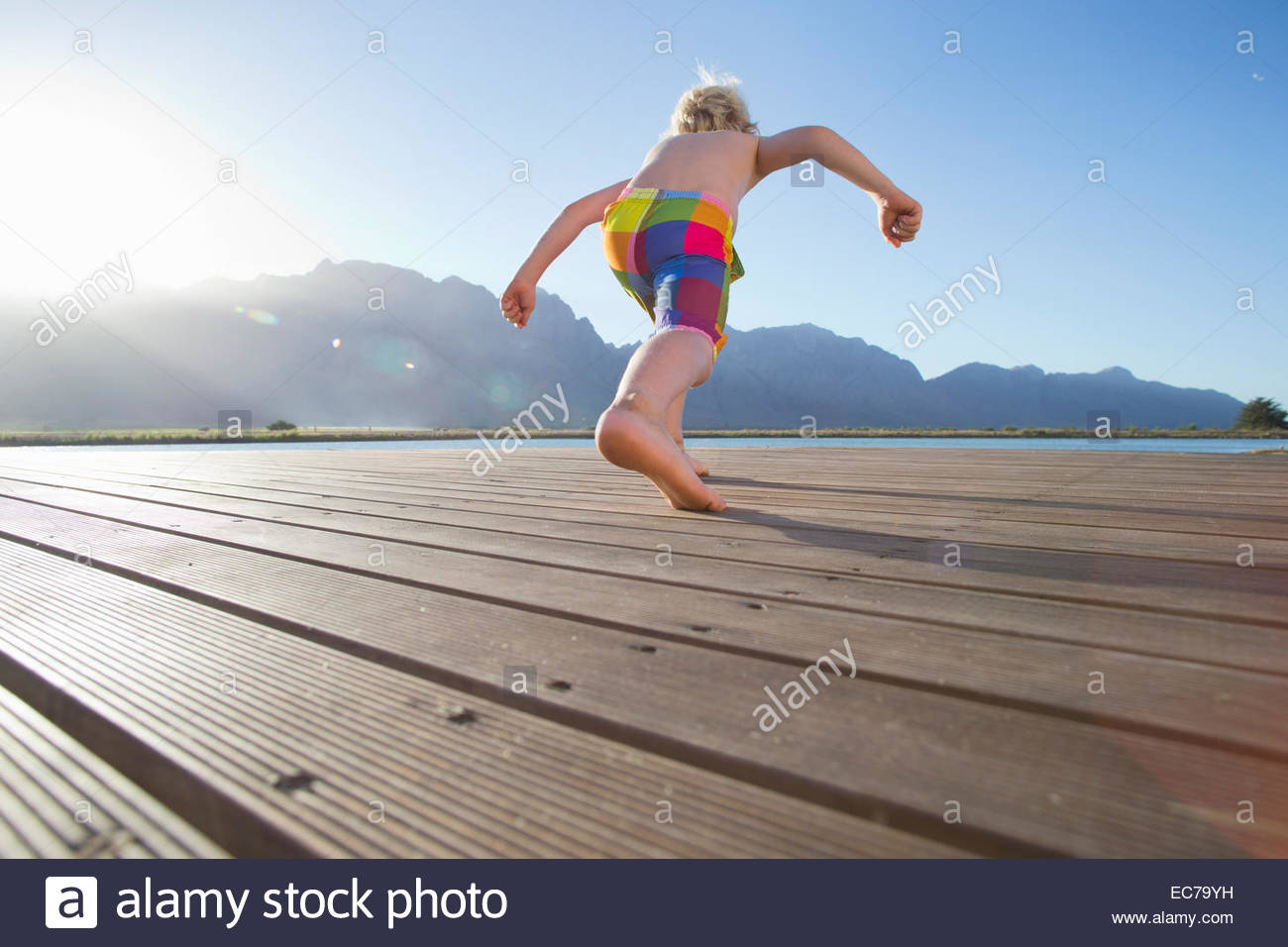 Boy running to jump into a lake from a jetty - Stock Image