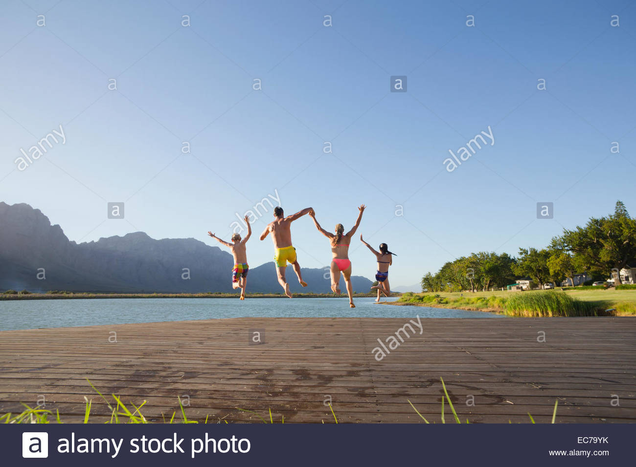 Family jumping into lake from a jetty - Stock Image