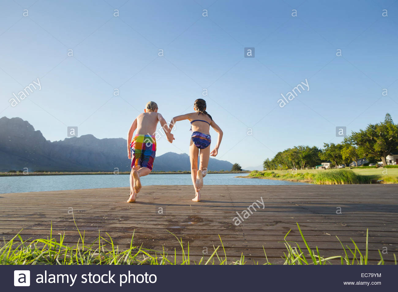 Children in swimwear, running to jump into a lake from a jetty - Stock Image