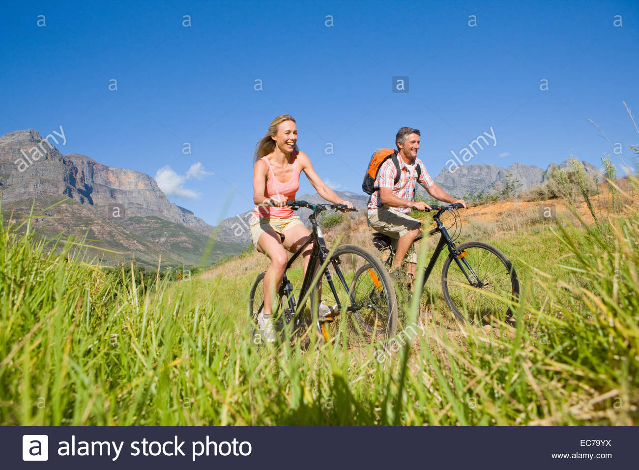 Couple mountain biking in countryside - Stock Image