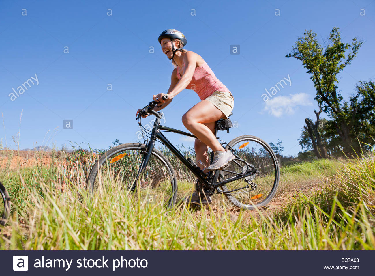 Woman mountain biking on country track - Stock Image