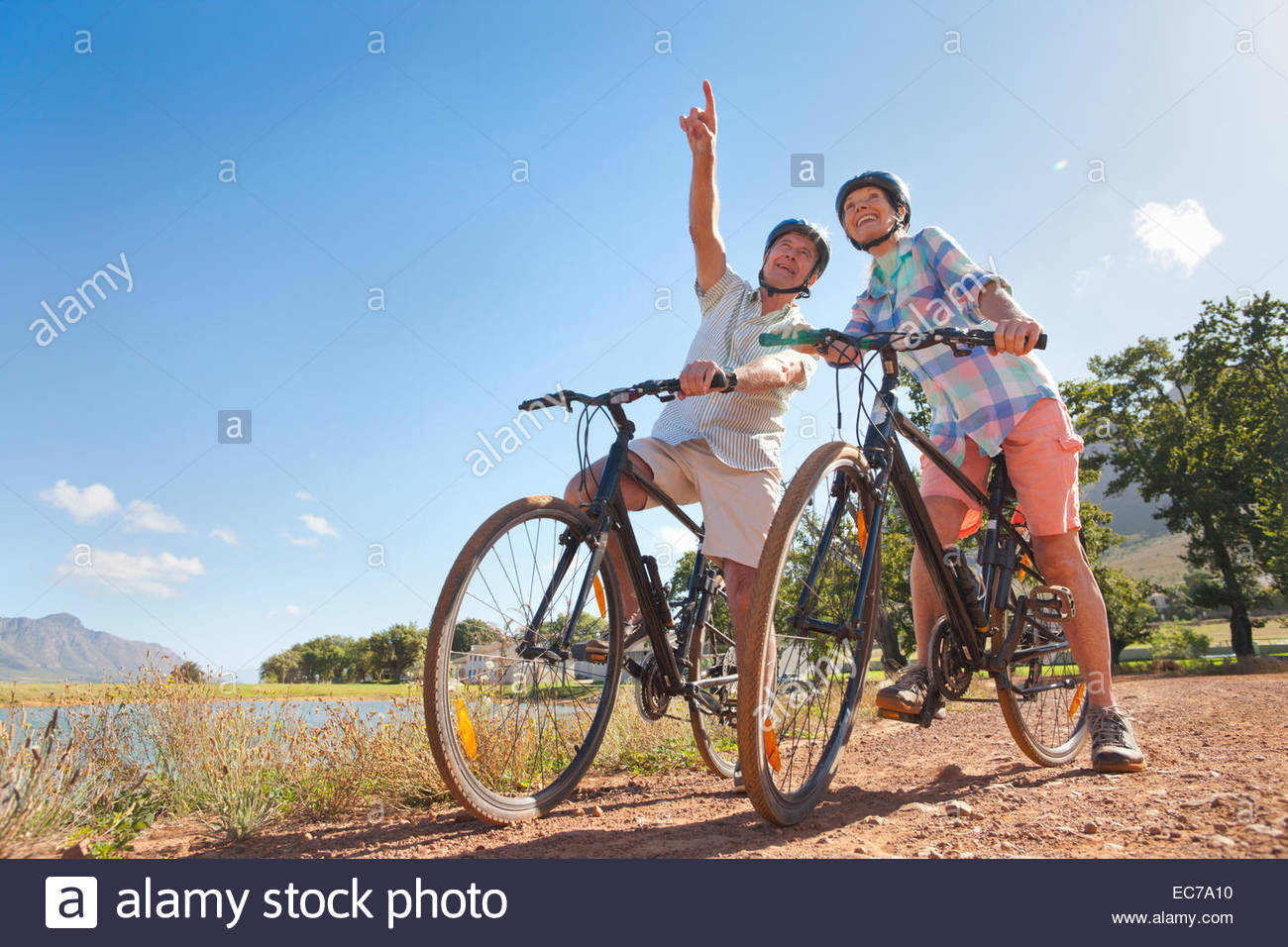Senior couple mountain biking on country track - Stock Image