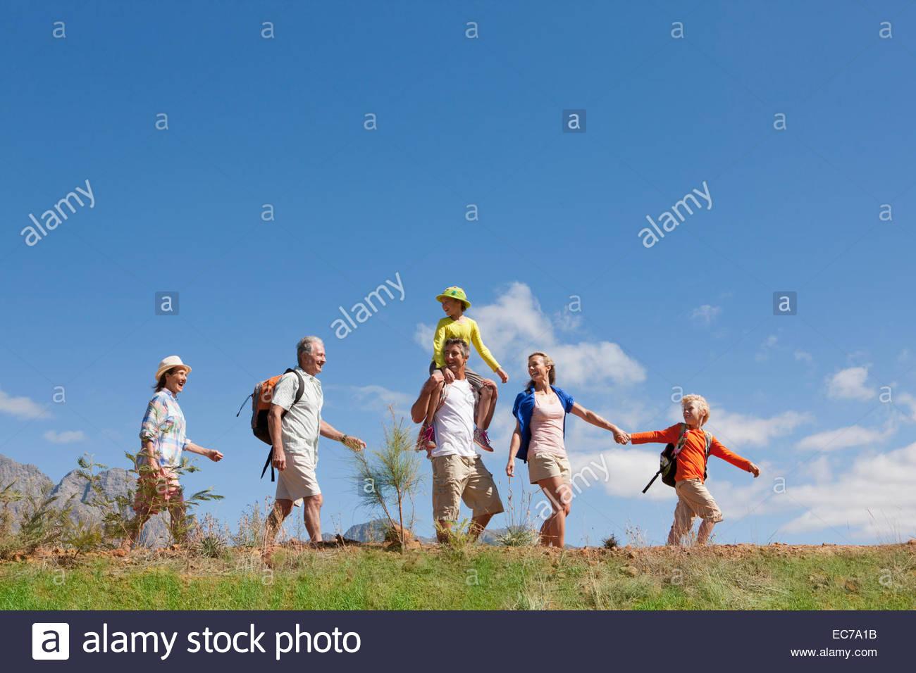 Multi generation family hiking on mountain path - Stock Image