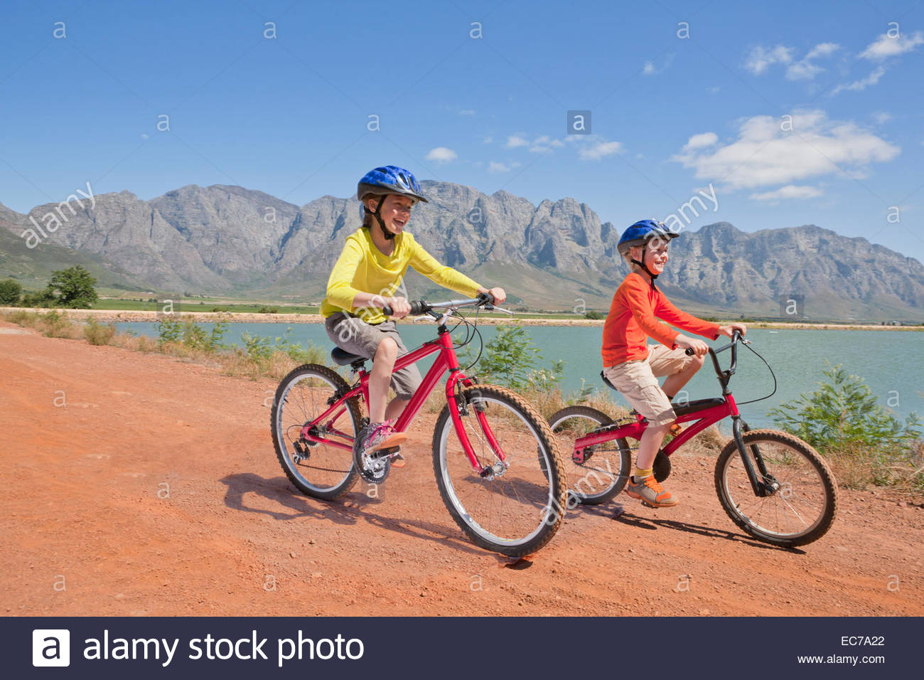 Children riding bicycles on track by lake - Stock Image