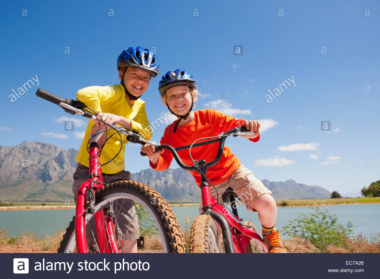 Portrait of children on mountain bikes by lake - Stock Image