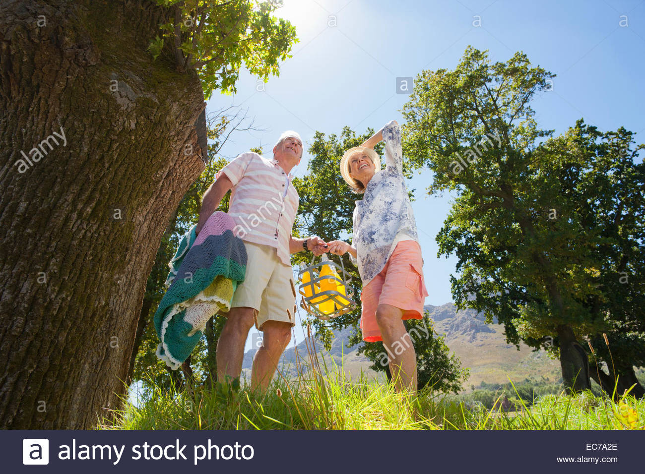 Senior couple with picnic bottles in countryside - Stock Image