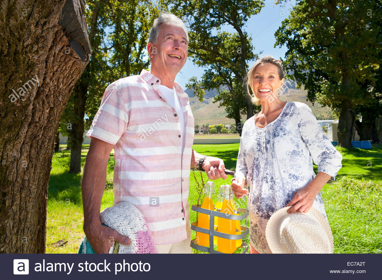 Senior couple with picnic bottles in countryside smiling at camera - Stock Image