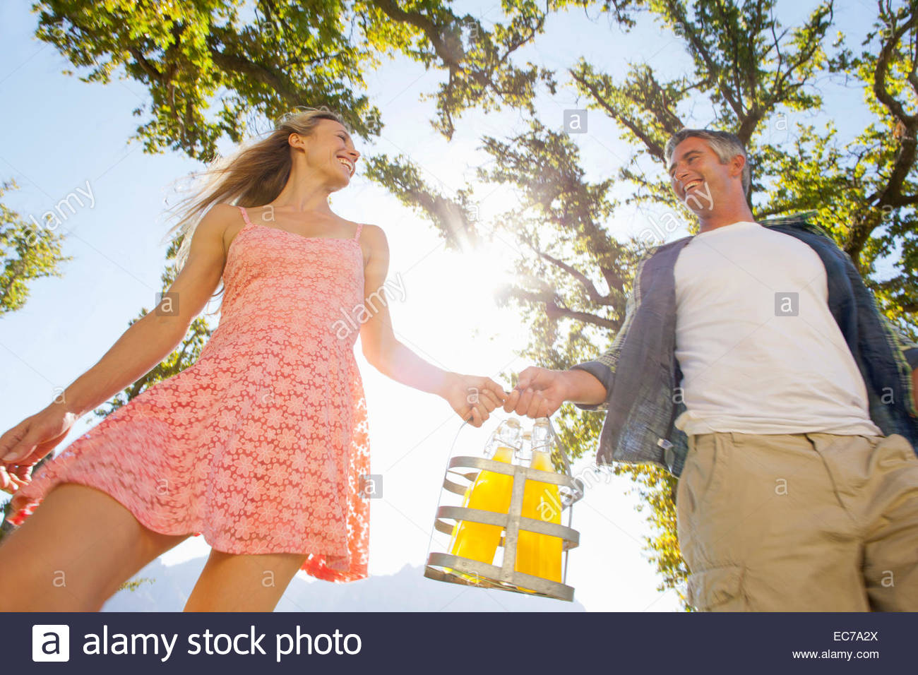Couple walking with picnic bottles in countryside - Stock Image