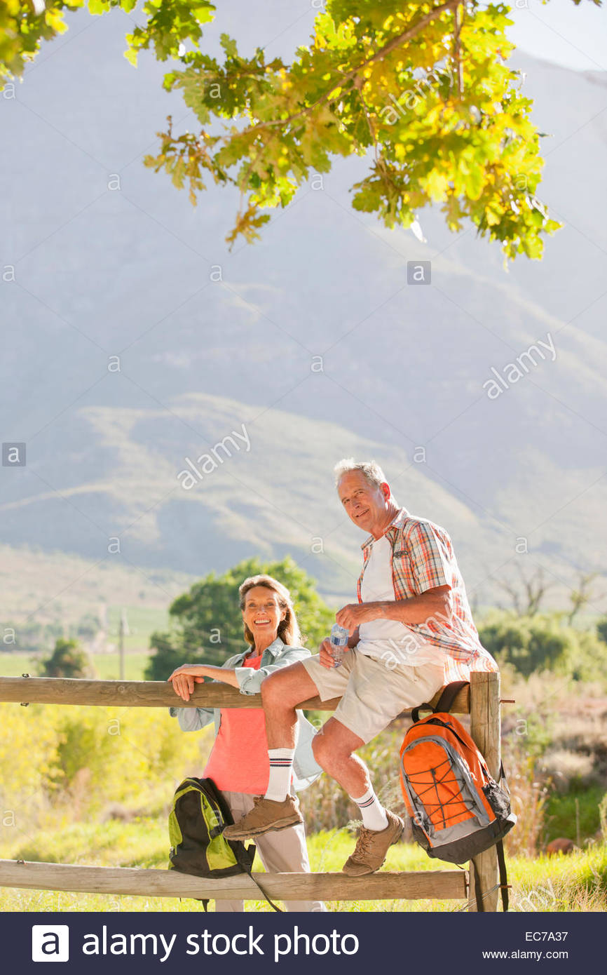Senior couple out for walk resting on a fence in countryside - Stock Image