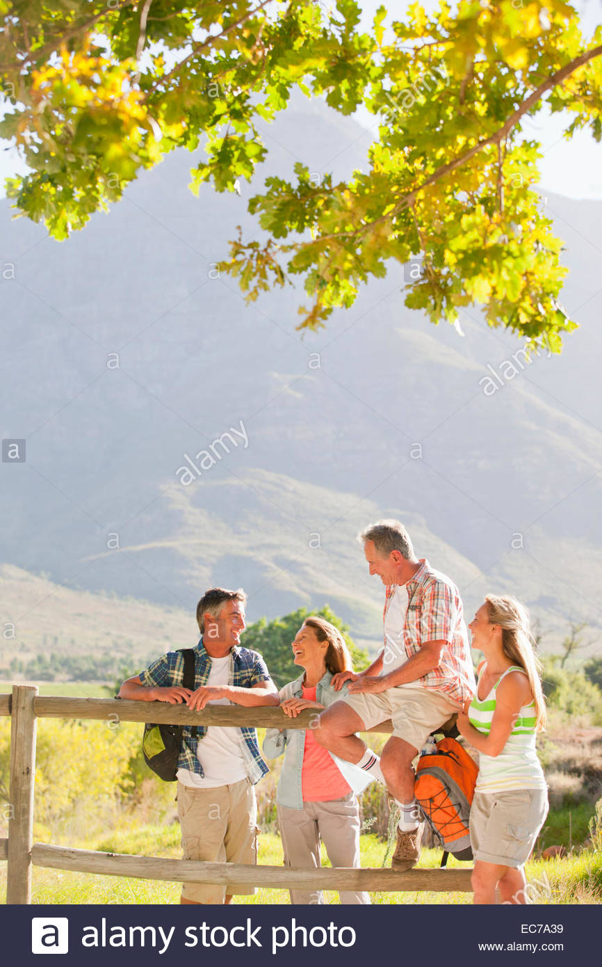 Two generation family out for walk resting on fence in countryside - Stock Image