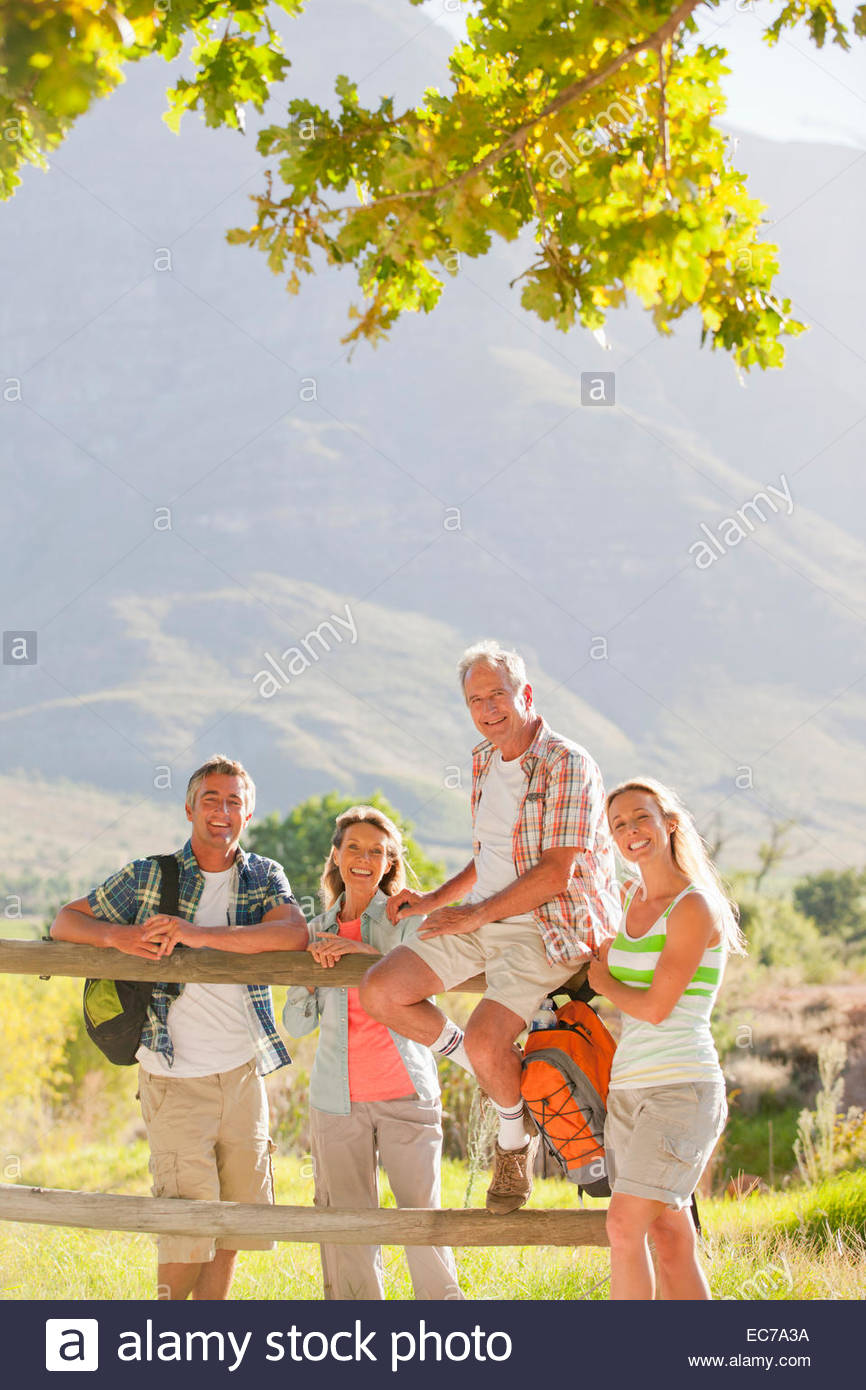 Two generation family out for walk resting on fence, smiling at camera, in countryside - Stock Image