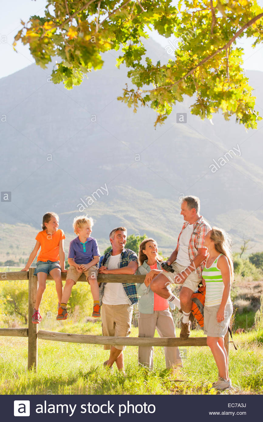 Multi generation family out for walk resting on a fence in a rural setting - Stock Image