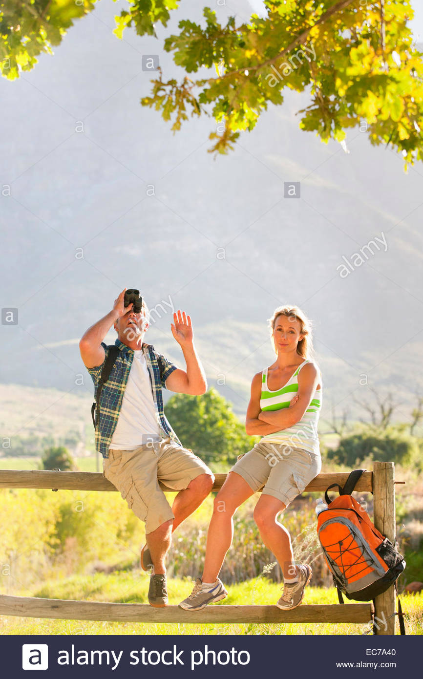 Couple out for walk resting on a fence in countryside - Stock Image