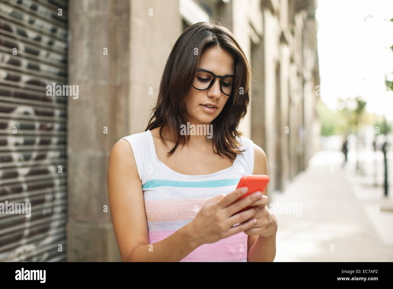 Young woman with smartphone reading SMS - Stock Image
