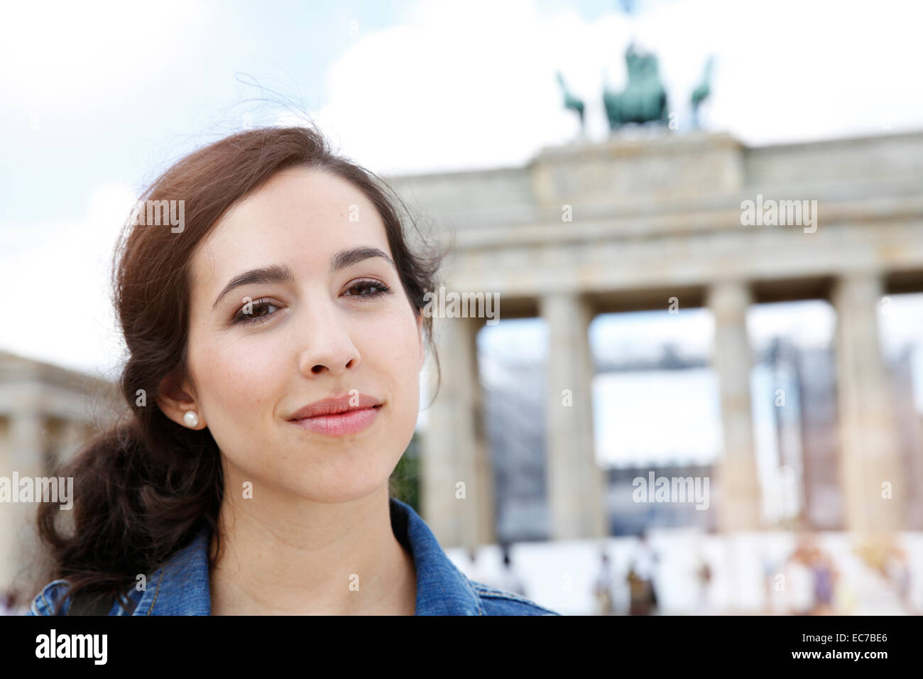 Germany, Berlin, portrait of young female tourist on city trip in front of Brandenburg Gate - Stock Image