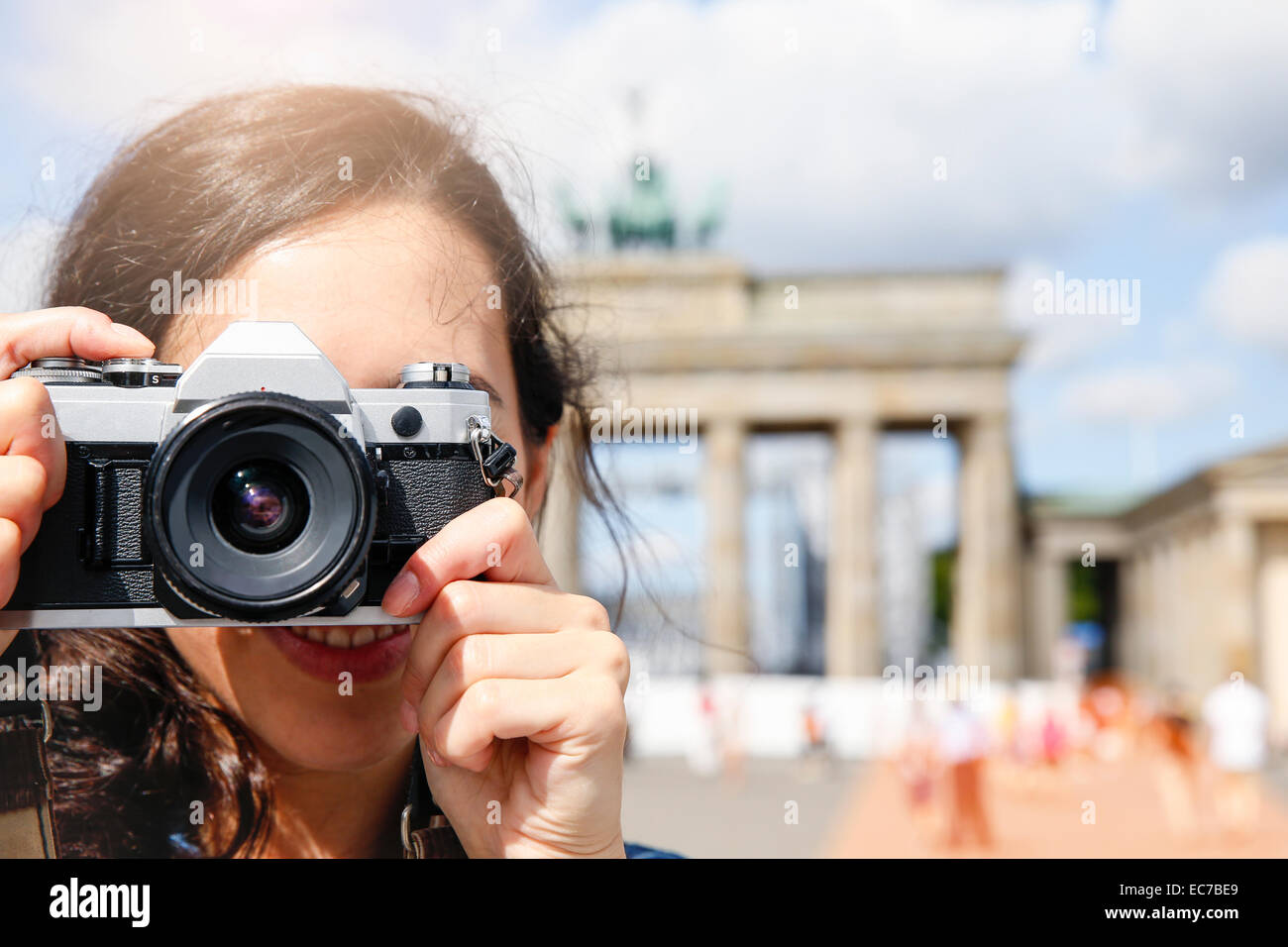 Germany, Berlin, female tourist standing in front of Brandenburg Gate photographing viewer - Stock Image