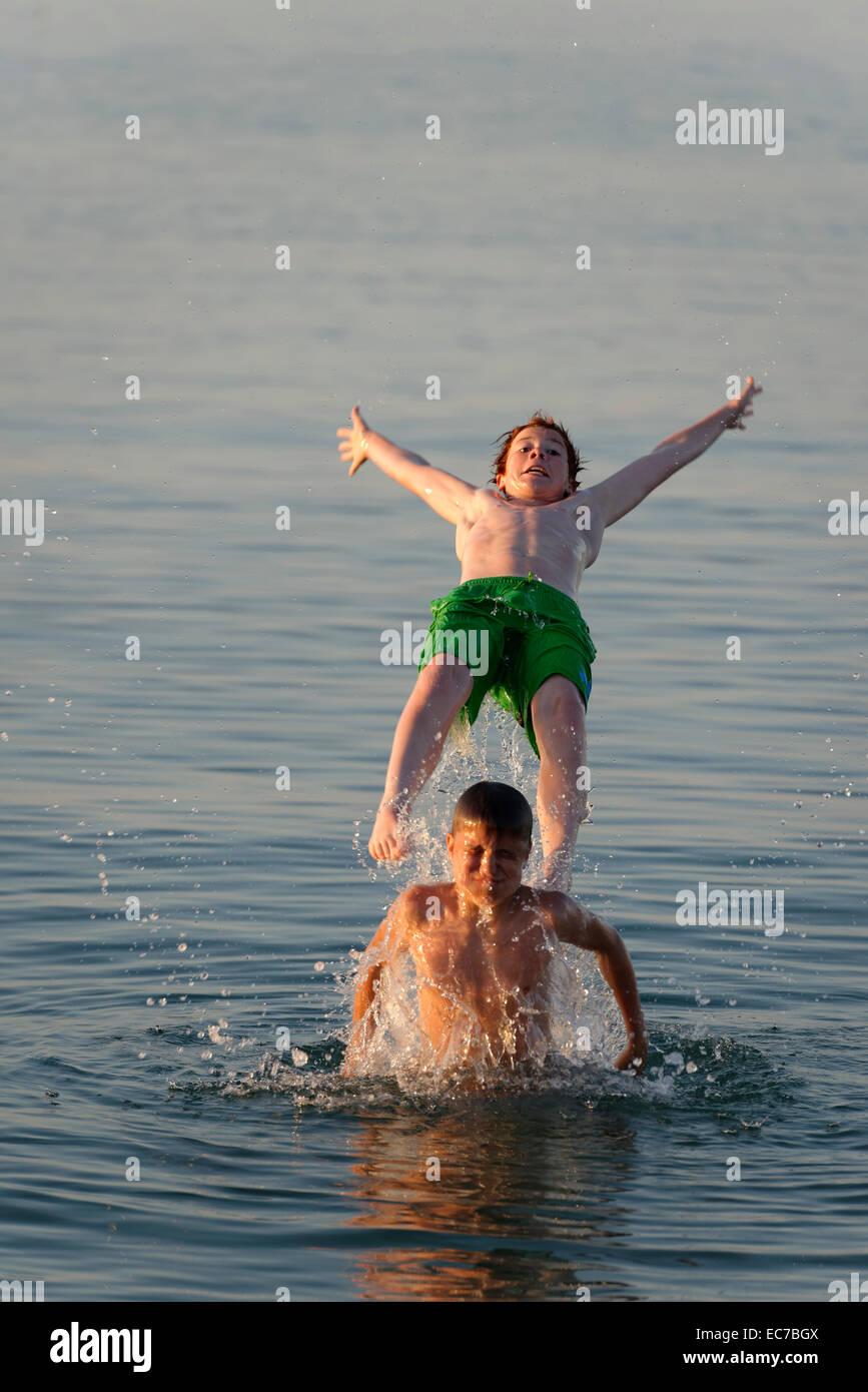 Italy, two teenage boys having fun at seaside - Stock Image