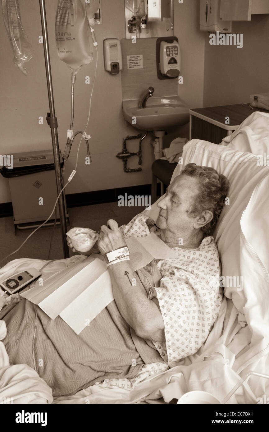 Ninety year old lady in NHS hospital having first meal following general anaesthetic. - Stock Image