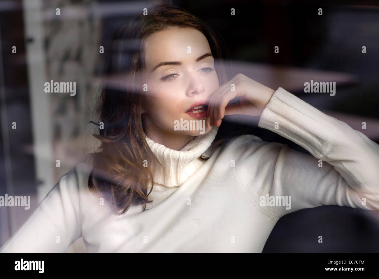 Portrait of pensive young woman looking through window pane of a cafe - Stock Image