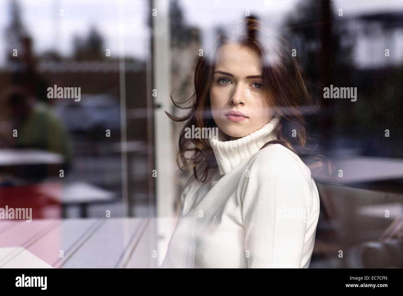 Portrait of young woman looking through window pane of a cafe - Stock Image
