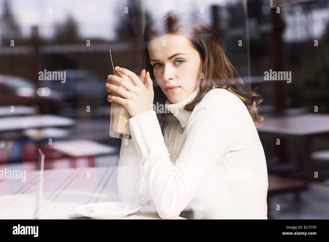 Portrait of young woman with Latte Macchiato sitting in a cafe looking through window pane - Stock Image