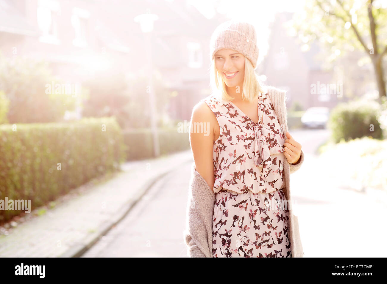 Portrait of smiling blond woman wearing patterned dress, cardigan and wool cap - Stock Image