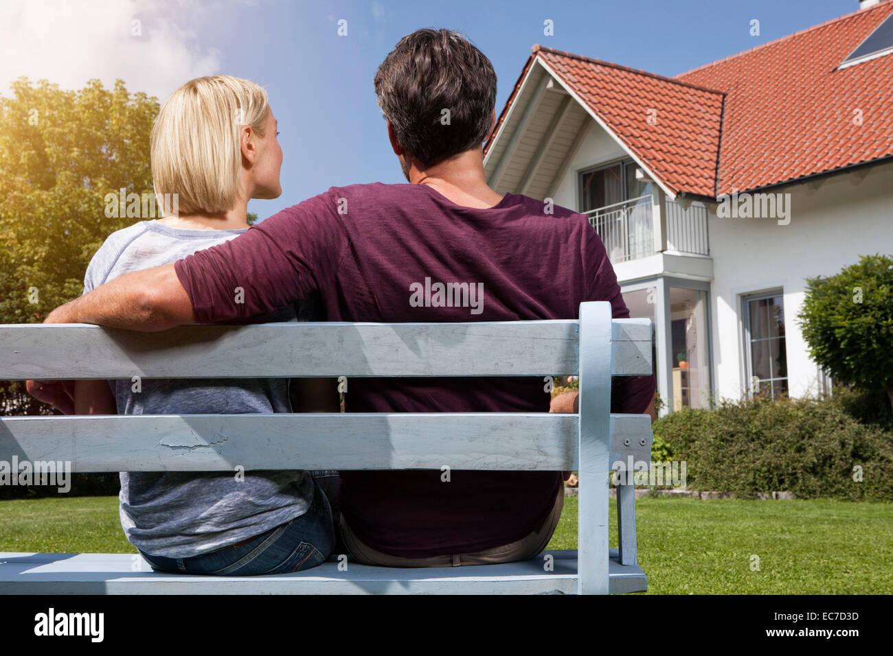 Rear view of mature couple sitting on bench in garden - Stock Image
