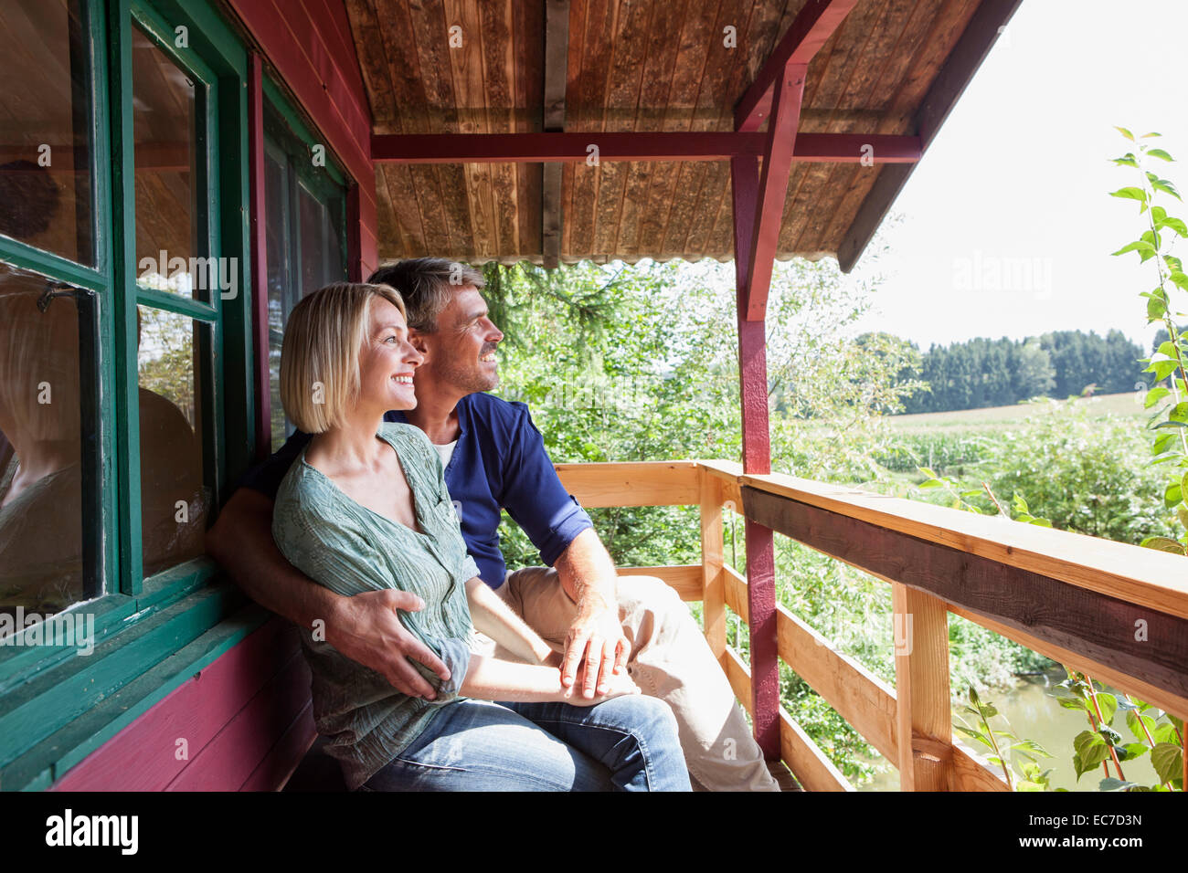 Happy mature couple on porch of summer house - Stock Image