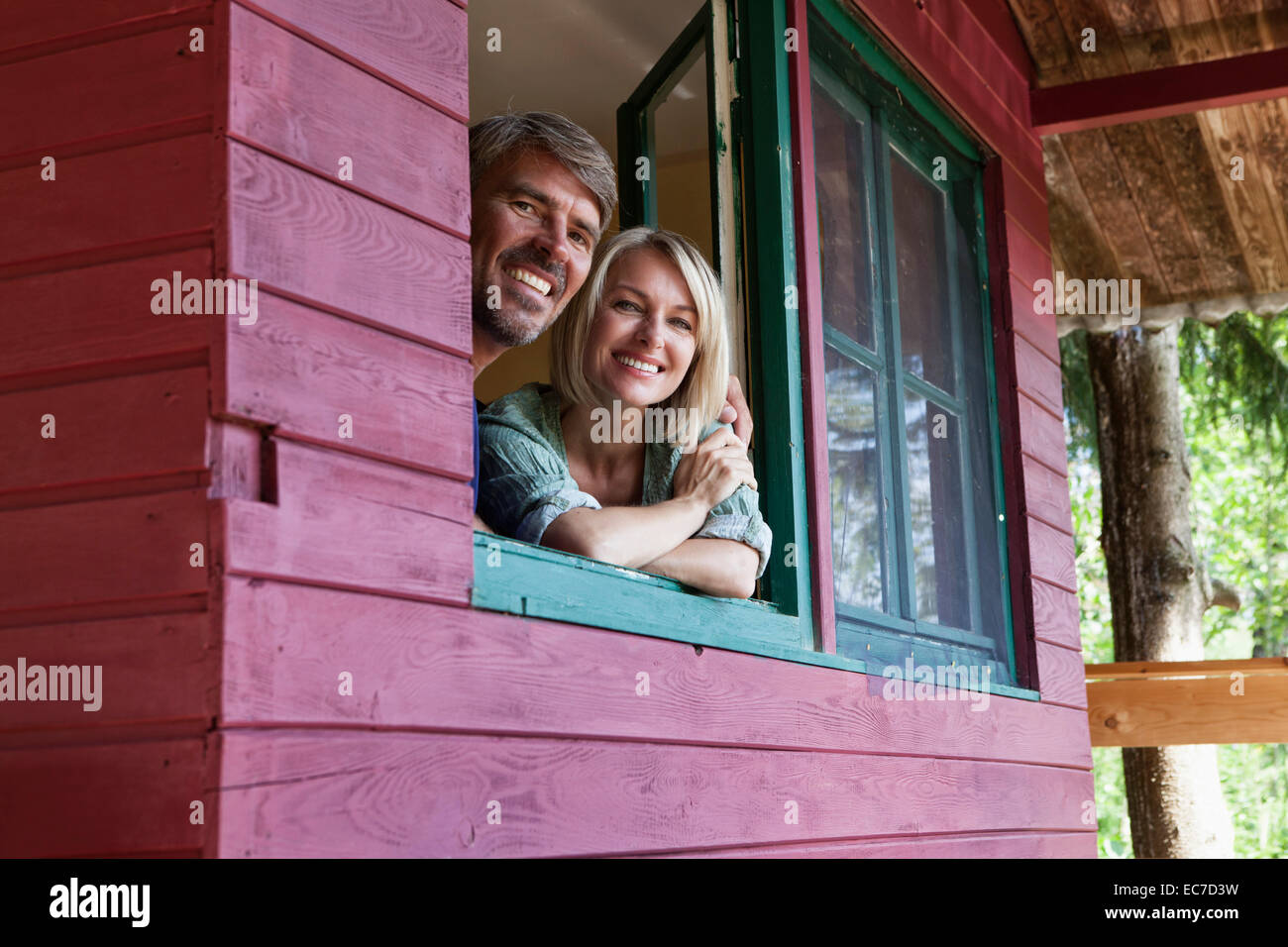 Happy mature couple looking out of window of summer house - Stock Image