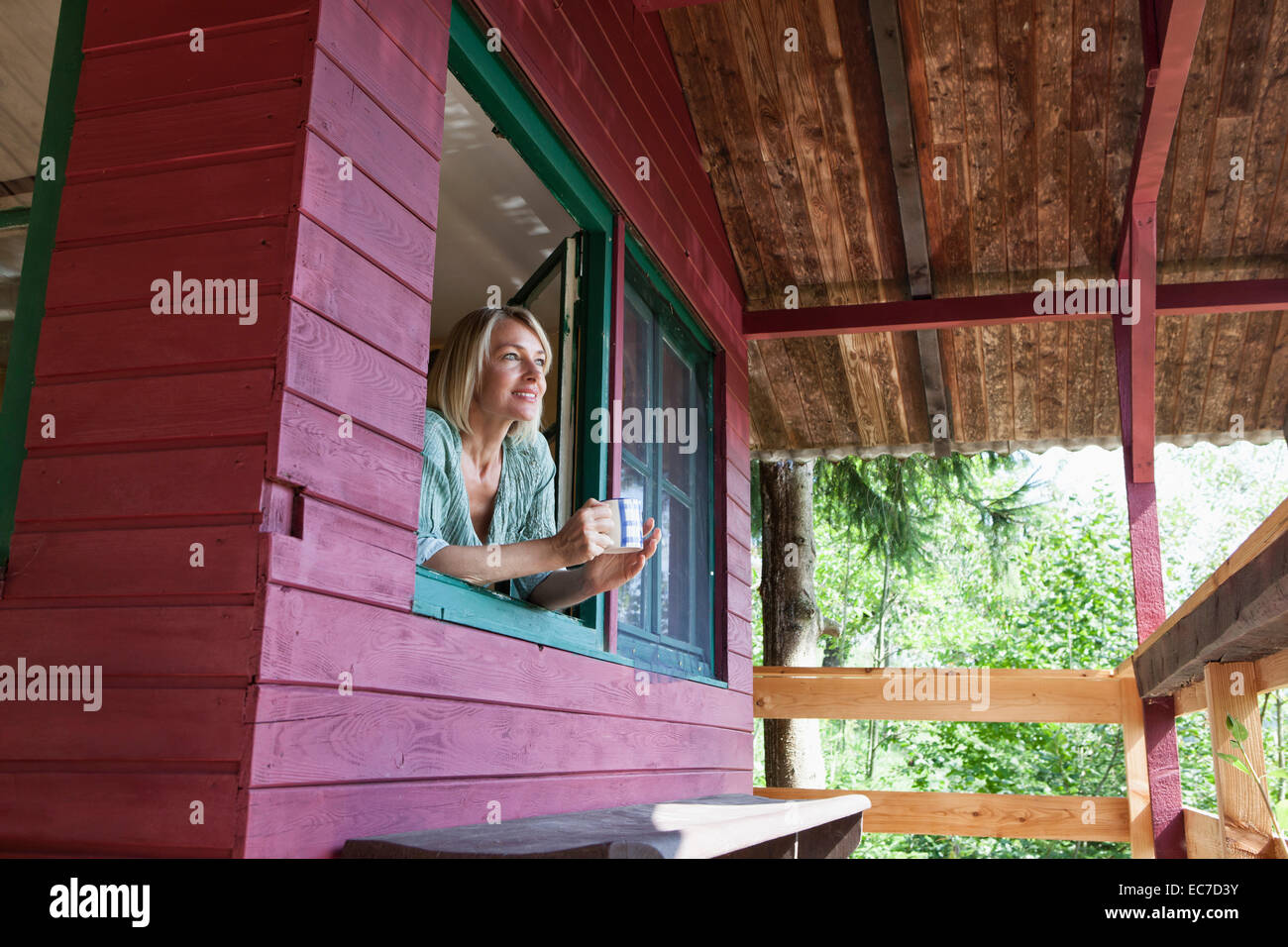 Smiling mature woman looking out of window of summer house - Stock Image