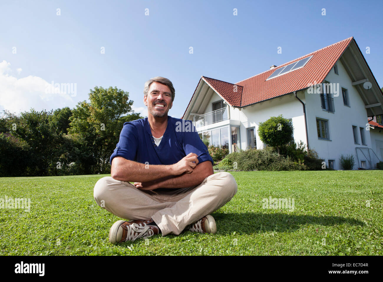 Smiling man sitting on lawn in garden Stock Photo