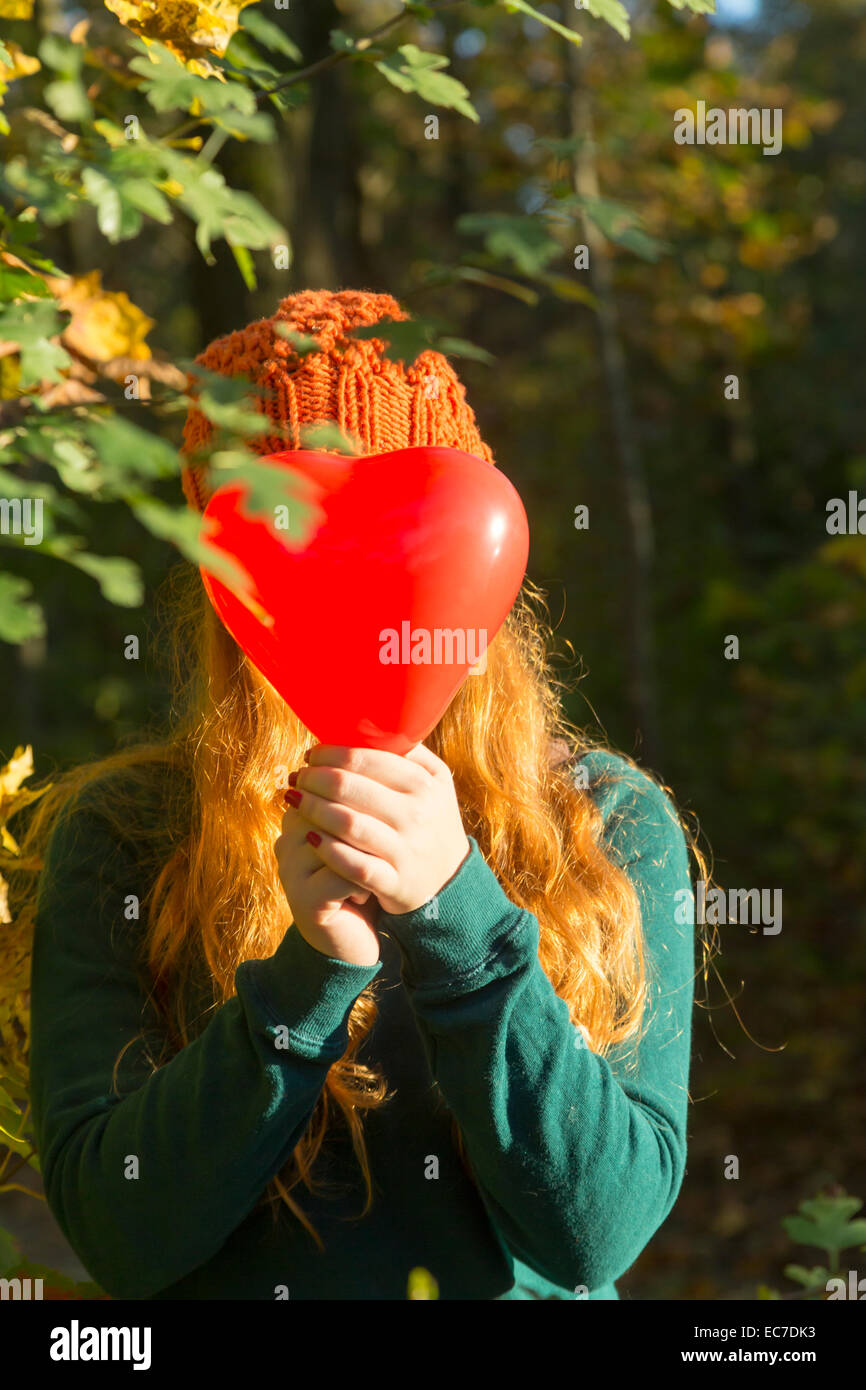 Teenage girl hiding her face behind heart shaped balloon - Stock Image