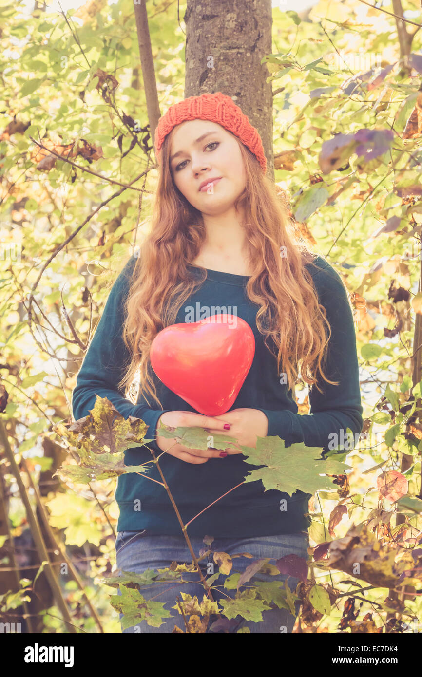 Teenage girl with heart shaped balloon leaning at a tree - Stock Image