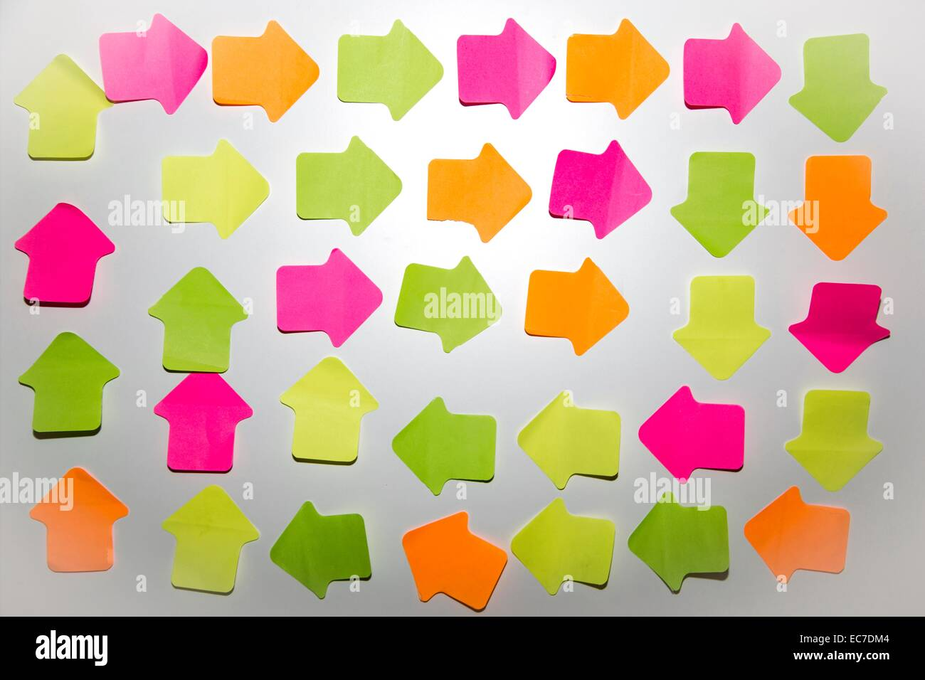 Coloured arrow shaped adhesive notes on white wall - Stock Image