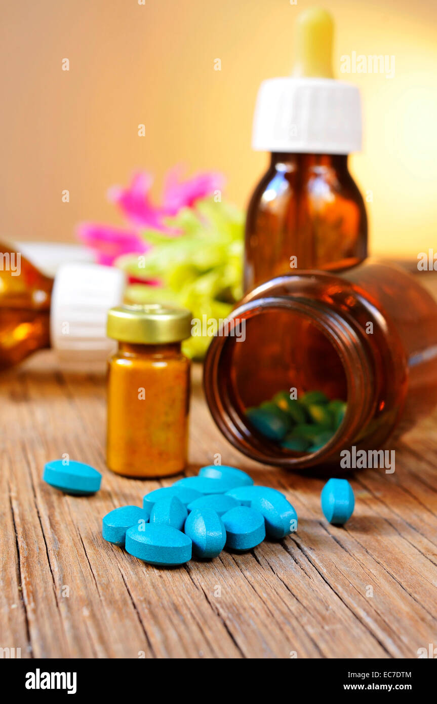 some bottles with different alternative remedies on a rustic wooden table Stock Photo