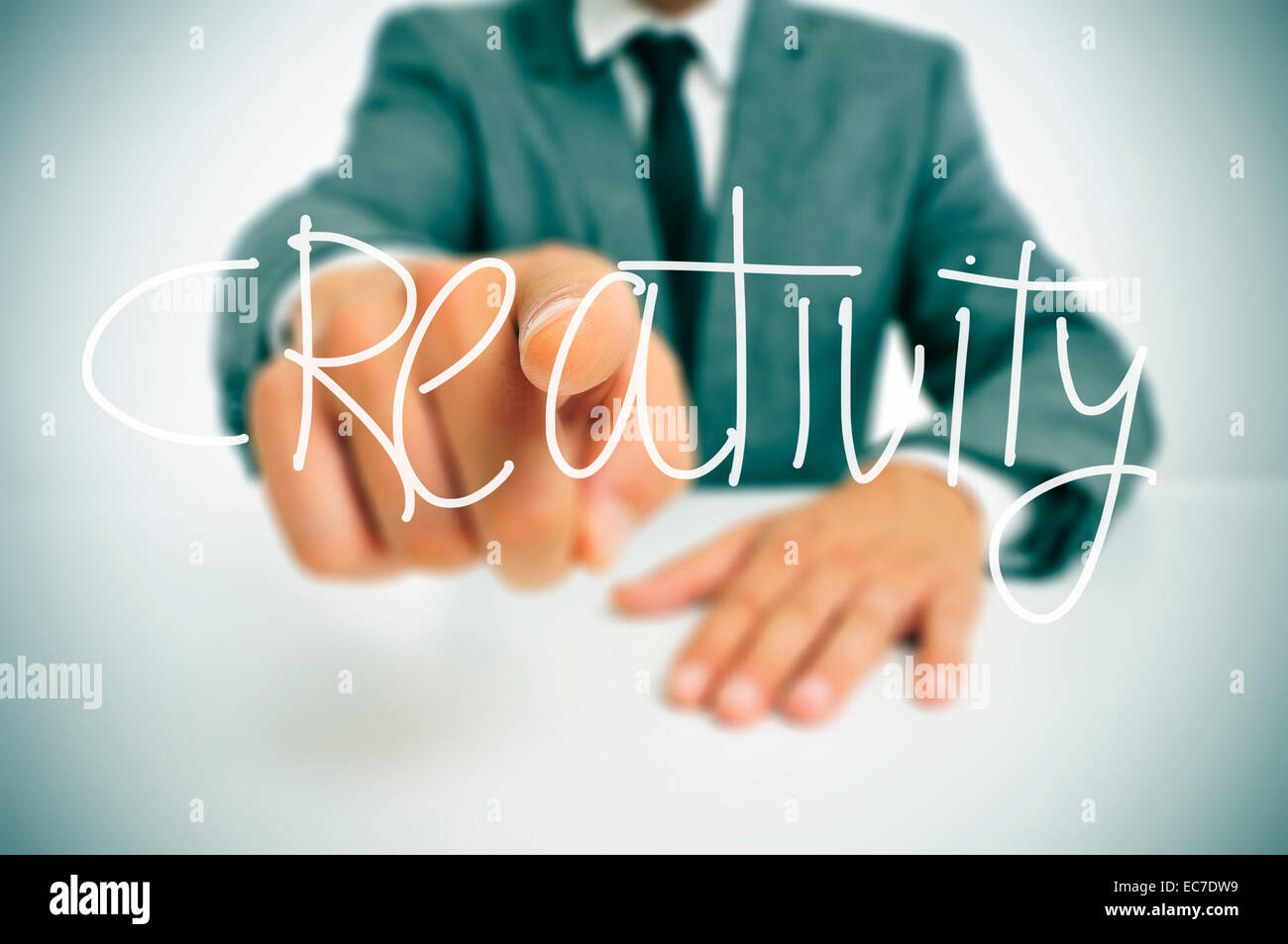 man in suit sitting in an office desk pointing the finger to the word creativity written in the foreground - Stock Image