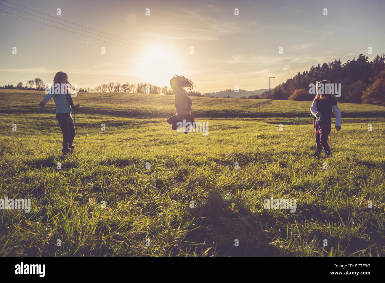 Three little girls playing with a spiral on a meadow in backlight - Stock Image